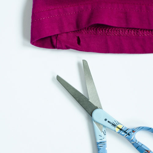 2. Cut a small hole in the hem at the bottom of the shirt
