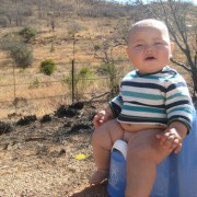 baby on potty chair at side of road during roadtrip