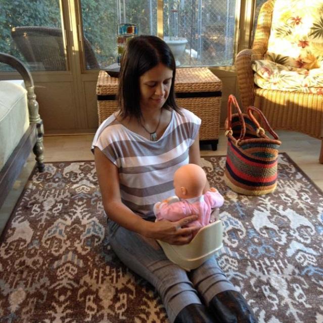 baby held on mini potty tilted
